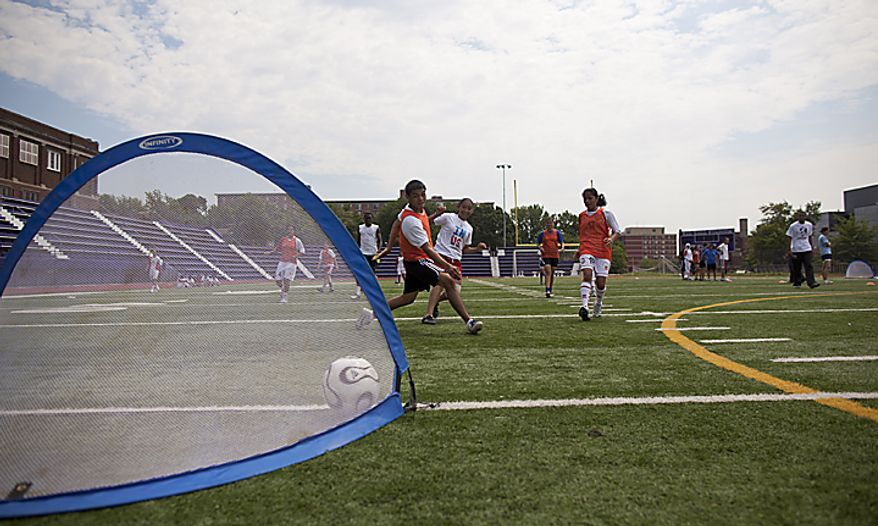 Athletes from Bell Multicultural High School and members of the UAE women's national soccer team mix up teams for a scrimmage during a soccer clinic at Cardozo High School in Northwest Washington, D.C. on Wednesday, July 13, 2011. (Pratik Shah/The Washington Times)