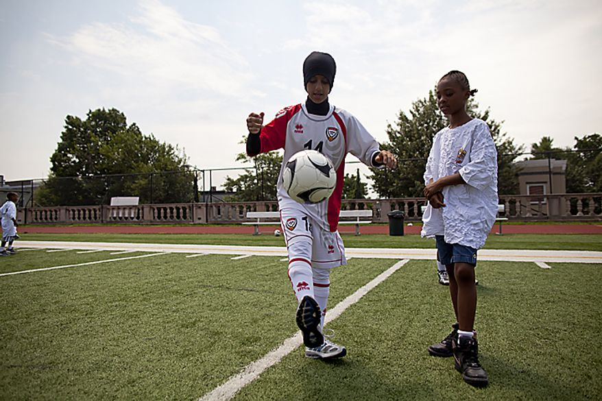Nada Al Huwait, 14, of the UAE women's national soccer team, helps teach a girl from the Boys and Girls Club of Greater Washington how to juggle during a soccer clinic at Cardozo High School in Northwest Washington, D.C. on Wednesday, July 13, 2011. (Pratik Shah/The Washington Times)
