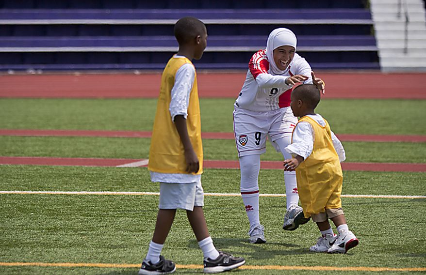 Alaa Ahmed Hassan, 9, of the UAE women's national soccer team, jokes around with Nathaniel Green Jr., from the Boys and Girls Club of Greater Washington during a soccer clinic at Cardozo High School in Northwest Washington, D.C., on Wednesday, July 13, 2011. (Pratik Shah/The Washington Times)