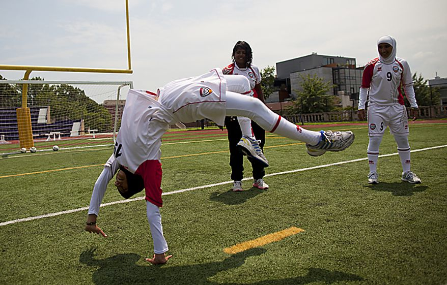 Shahad Ahmed Budebs, 19, of the UAE women's national soccer team does a backflip as teammates Houriya Taheri (left) and Alaa Ahmed Hassan watch during a soccer clinic at Cardozo High School in Northwest Washington, D.C. on Wednesday, July 13, 2011. (Pratik Shah/The Washington Times)