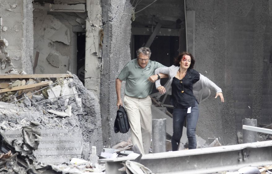 An injured woman is assisted from a damaged building in Oslo, Friday, July 22, 2011, after an explosion rocked the capital. Terrorism ravaged long-peaceful Norway on Friday when a bomb ripped open buildings including the prime minister's office and a man dressed as a police officer opened fire at a nearby island youth camp. (AP Photo/Scanpix, Morten Holm)