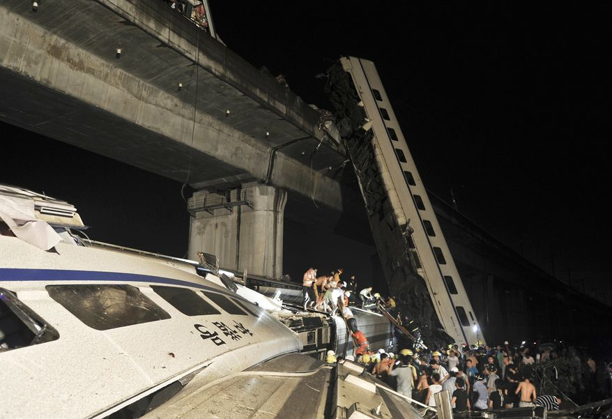 Emergency workers and people work to help passengers from the wreckage of train after two carriages from a high-speed train derailed and fell off a bridge in Wenzhou in east China's Zhejiang province on Saturday, July 23, 2011. (AP Photo)