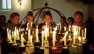 "People light candles at Oslo Cathedral on Sunday in memory of the victims of the attacks on Norway's government headquarters and an island youth retreat. ""We are a people in mourning,"" Bishop Ole Christian Kvarme said during an emotion-filled Mass attended by members of the Norwegian government, the royal family and the general public. (Associated Press)"