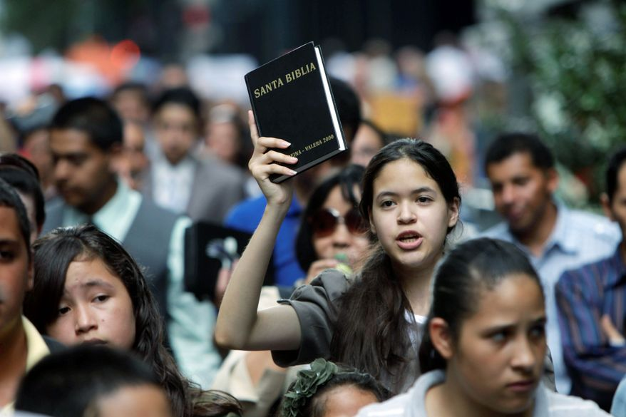 A girl raises a bible above her head while marching with protesters against gay marriage in New York on Sunday. (Associated Press)