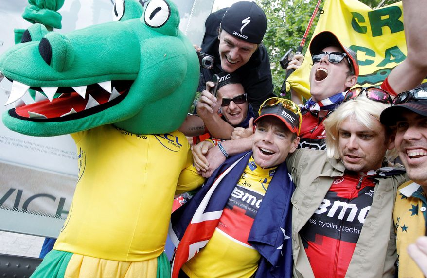 ASSOCIATED PRESS PHOTOGRAPHS Tour de France winner Cadel Evans, wearing the overall leader's yellow jersey, celebrates with fans during the victory parade in Paris. Below, supporters awaited his victory lap after the podium ceremony.