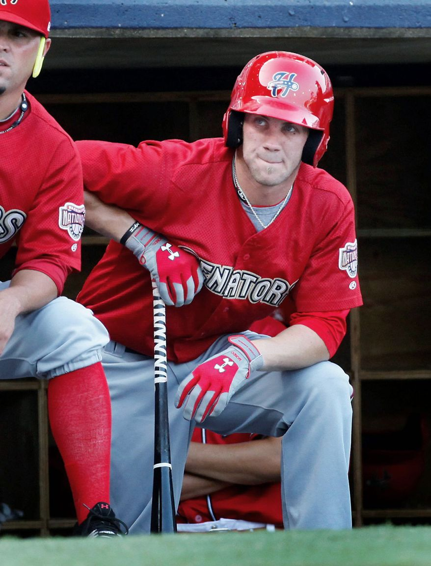 Bryce Harper, who was chosen by the Washington Nationals with the top pick in last year's draft, waits in the dugout during the first inning during the Harrisburg Senators' Double-A baseball game against the Richmond Flying Squirrels in Richmond, Va., on Thursday, July 21, 2011. (AP Photo Richmond Times-Dispatch, Dean Hoffmeyer)