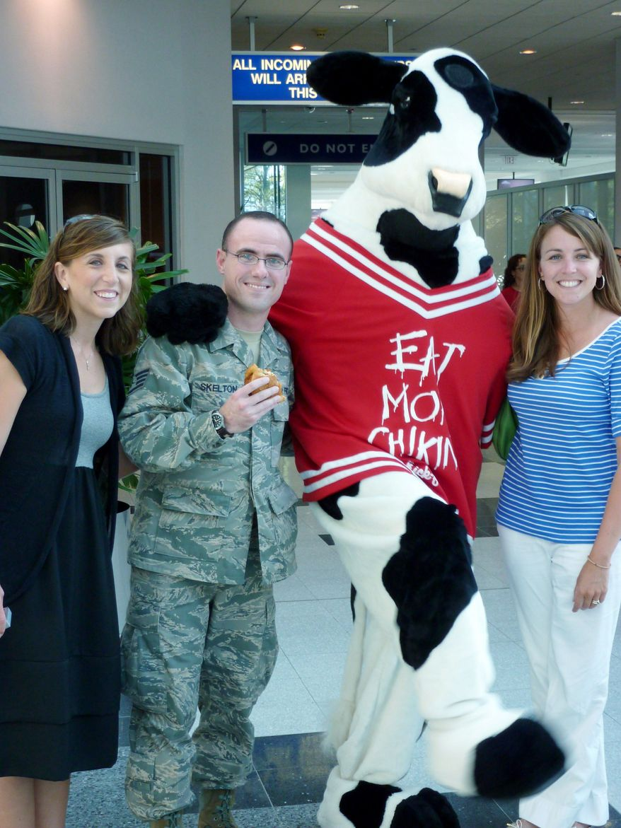 Ben Skelton of Concord, N.C., poses with Katie Harris, marketing director of the Chick-fil-A in West Columbia, S.C. (left) and Britt Sims, owner and operator of the Chick-fil-A in West Columbia, S.C. and the Chick-fil-A cow mascot. Mr. Skelton plans for the mascot to be the best man at his October wedding. (Associated Press)