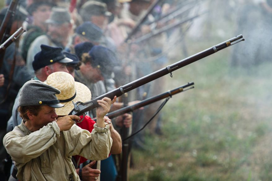 Confederate infantry fires on the Union during the 150th Anniversary of the Battle of First Manassas/Bull Run Reenactment. (Drew Angerer/The Washington Times)