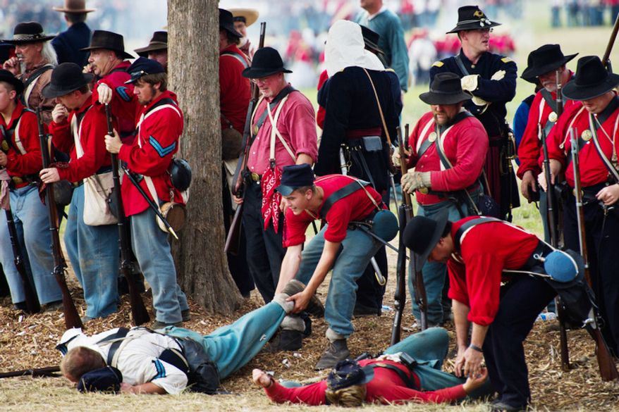 Union soldiers pull wounded troops off the battlefield. (Drew Angerer/The Washington Times)