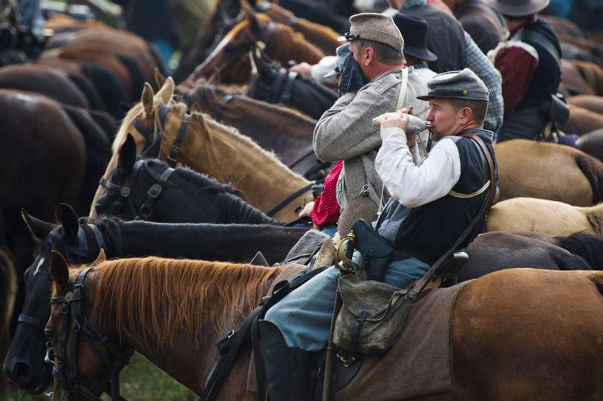 A Union soldier takes a break on his horse to sip from his canteen to stay cool during the 150th Anniversary of the Battle of First Manassas/Bull Run Reenactment. (Drew Angerer/The Washington Times)