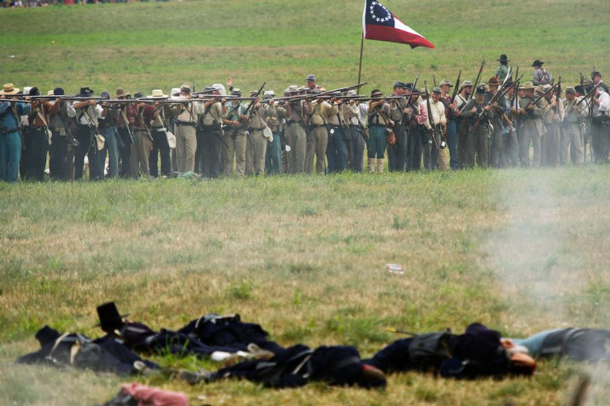 With wounded Union soldiers in the foreground, Confederate troops fire their muskets on the Union position during the 150th Anniversary of the Battle of First Manassas/Bull Run Reenactment, at Pageland Farm, in Gainesville, Va., Sunday, July 24, 2011. The battle was the first major land battle in the Civil War and the South was victorious.(Drew Angerer/The Washington Times)