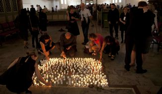 People light candles after a service at Oslo Cathedral in the aftermath of the attacks on Norway's government headquarters and a youth retreat in Oslo, Sunday, July 24, 2011. The man blamed for the attacks said he was motivated by a desire to bring about a revolution in Norwegian society, his lawyer said Sunday. (AP Photo/Matt Dunham)