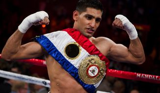 Amir Khan, of Bolton, England, celebrates his fifth round TKO victory over Zab Judah just after their IBF & WBA junior welterweight title boxing match on Saturday at Mandalay Bay Resort & Casino in Las Vegas. (AP Photo/Eric Jamison)