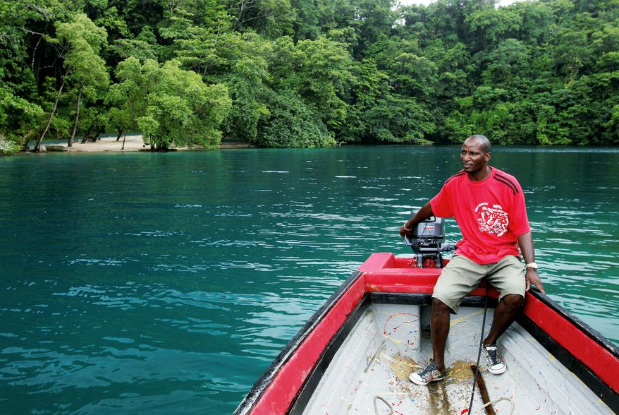 Cy Mortluck, 35, waits in his boat for tourists in the Blue Lagoon. One of Jamaica's most breathtaking natural attractions, the lagoon is popular among locals and tourists. But, with increasing pressure from the government to create jobs and build up the area, the Blue Lagoon could become less isolated and majestic. (Associated Press)