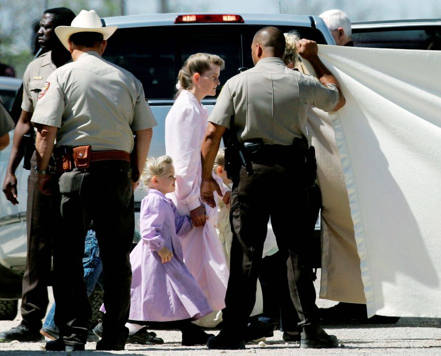 ASSOCIATED PRESS PHOTOGRAPHS Members of the Fundamentalist Church of Jesus Christ of Latter-day Saints are assisted by law-enforcement officials to board a San Angelo Independent School District bus that is being used to relocate them from Eldorado, Texas, to San Angelo, Texas.