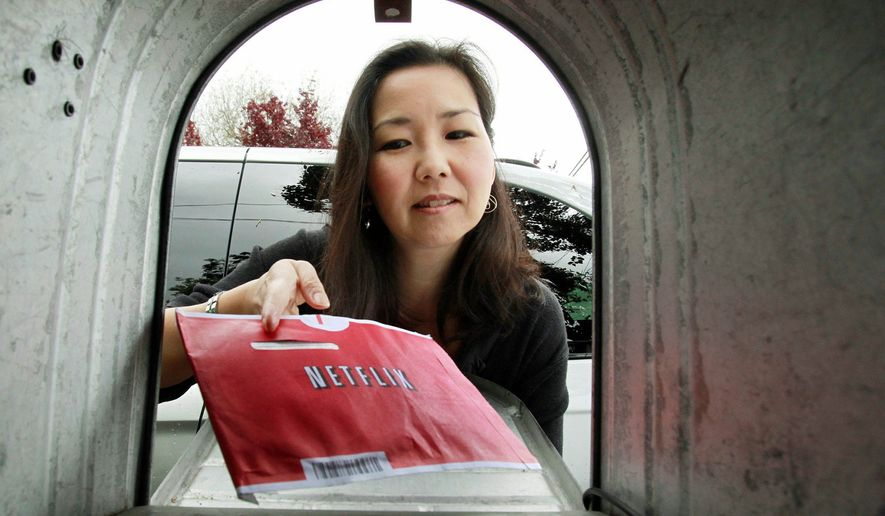 Carleen Ho pulls a Netflix movie out of her mail box in Palo Alto, Calif. Netflix provoked the ire of some of its 23 million subscribers by raising its prices by as much as 60 percent for those who want to rent DVDs by mail and watch video on the Internet. (Associated Press)