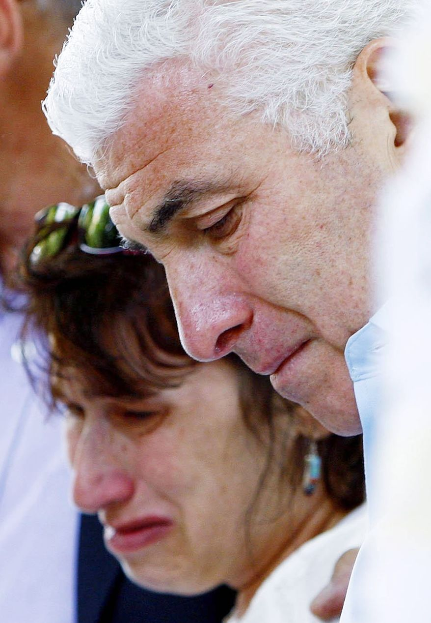 Amy Winehouse's parents Mitch and Janis weep as they view floral tributes outside their daughter's home in London's Camden Square on July 25, 2011. (Associated Press)