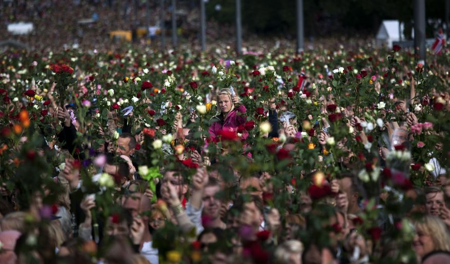 """People gather outside Oslo City Hall to participate in a """"rose march"""" in memory of the victims of Friday's bomb attack and shooting massacre, Norway, Monday, July 25, 2011. (AP Photo/Emilio Morenatti)"""