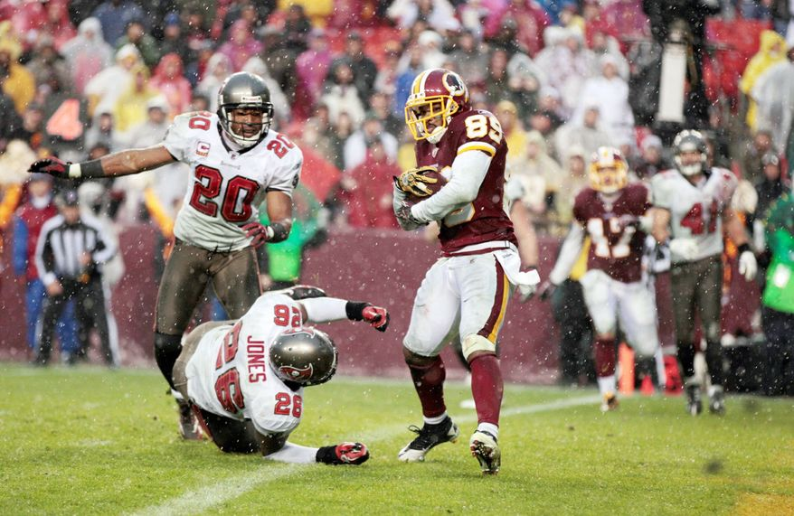 Washington Redskins wide receiver Santana Moss catches a touchdown pass in front of Tampa Bay Buccaneers cornerback Ronde Barber and safety Sean Jones on Sunday, Dec. 12, 2010. Tampa Bay defeated the Redskins 17-16. (AP Photo/Rob Carr)