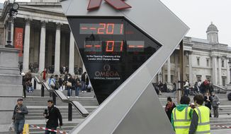 "In this Tuesday March 15, 2011 file photo, the official London 2012 Olympic countdown clock is attended to by technicians hours after it was started in Trafalgar Square in London. A year from now, London will be at the center of global attention when it hosts the opening ceremony of what organizers call the ""greatest show on earth,"" the 2012 Olympics.. (AP Photo/Alastair Grant, File)"