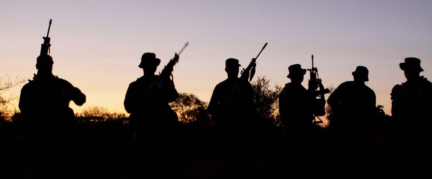 Armed South African soldiers stage a night patrol (below) for visiting news media reporting on their efforts to counter rhino poachers. (Associated Press)