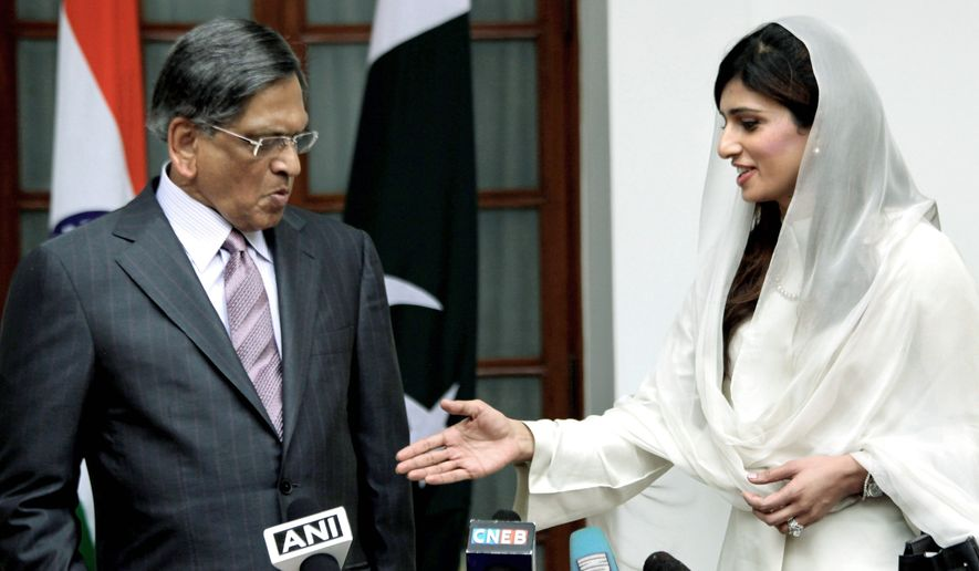 Indian Foreign Minister S.M. Krishna (left) reacts as his Pakistani counterpart, Hina Rabbani Khar, reaches out to shake hands before their talks in New Delhi on Wednesday. The ministers met Wednesday for the first time since the nuclear-armed rivals resumed peace talks in February. Those talks were suspended after Pakistan-based militants attacked the city of Mumbai in November 2008. (Associated Press)