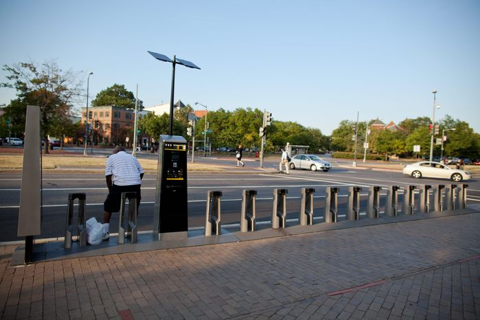 A man sits at an empty Capital Bikeshare stand near the Eastern Market Metro station in Southeast. Riders can check a station's status on a free GPS-enabled mobile application or Bikeshare's website. (Pratik Shah/The Washington Times)