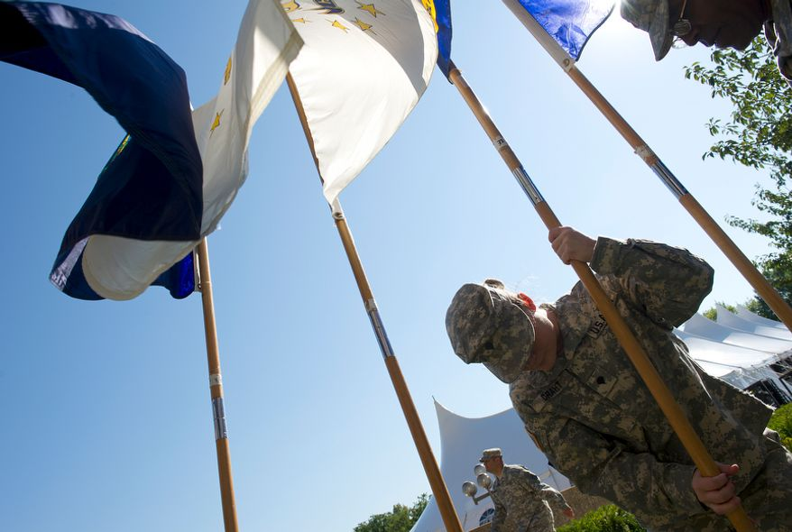 "SPC E4 Erika Draht, U.S. Army, adjusts one of the 50 state flags outside of Walter Reed Army Medical Center before a ceremony to officially ""case the colors"" as a transition to medical services at Bethesda Naval Medical Center and Ft. Belvoir. Casing the colors involves retiring the flags that have served as the symbols of the different medical units. (Barbara L. Salisbury/The Washington Times)"