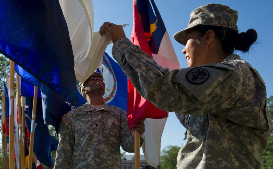 """SPC E4 Lazaro Mtunguja, left, and Sgt. Betsy Rodriguez, both U.S. Army, adjust some of the 50 state flags outside of Walter Reed Army Medical Center Wednesday, July 27, 2011 before a ceremony  to officially """"case the colors"""" as a transition to medical services at Bethesda Naval Medical Center and Ft. Belvoir. Casing the colors involves retiring the flags that have served as symbols of the various medical units. (Barbara L. Salisbury/The Washington Times)"""