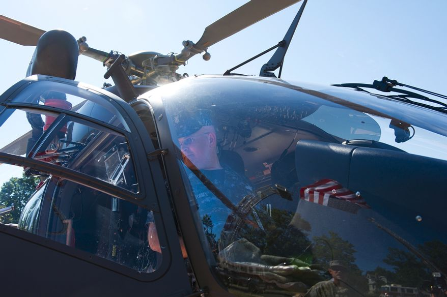 """Shawn Forbes, IT1 E6, U.S. Navy, sits inside an Army medical helicopter while the U.S. flag is reflected in the helicopter's nose outside of Walter Reed Army Medical Center. The helicopter and flag were part of a static display for visitors at a ceremony to officially """"case the colors"""" as a transition to medical services at Bethesda Naval Medical Center and Ft. Belvoir. The official close date of Walter Reed is Sept. 15. (Barbara L. Salisbury/The Washington Times)"""