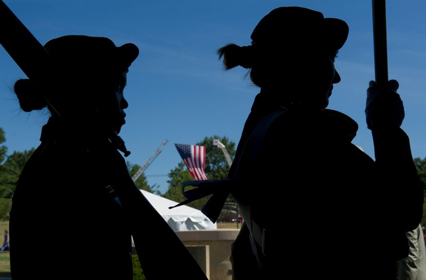 "Members of the Army Color Guard wait to bring in the flag while a large U.S. flag hangs from firetrucks behind them at Walter Reed Army Medical Center in Washington, D.C., on Wednesday, July 27, 2011. The medical center held a ceremony Wednesday to officially ""case the colors"" as a transition to medical services at Bethesda Naval Medical Center and Ft. Belvoir. The flags of the various Walter Reed medical units were retired by rolling them up and covering them. (Barbara L. Salisbury/The Washington Times)"