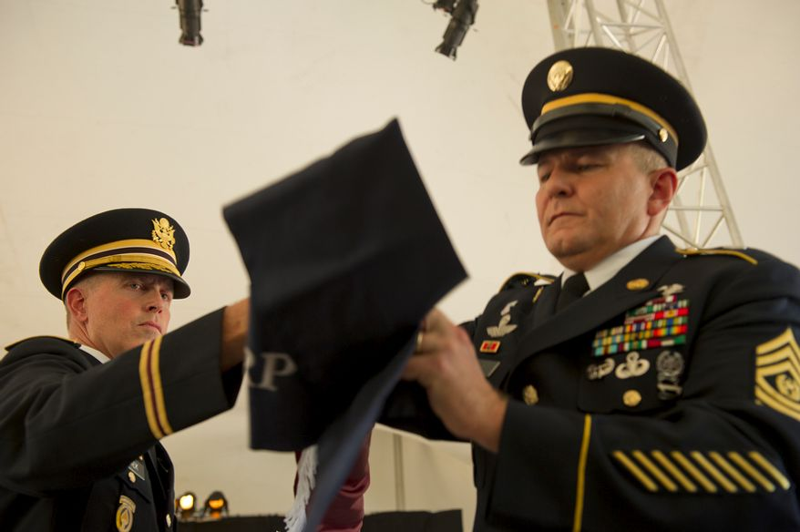 """Col. William Schiek, left, and CSM Steven Craig retire (or """"case"""") the Medical Center Brigade flag by rolling it up and covering it during a ceremony Wednesday, July 27, 2011 at Walter Reed Army Medical Center in Washington, D.C. The flags of the various medical units at Walter Reed were all retired during the ceremony as a means of transitioning from the Washington, D.C., facility to Ft. Belvoir and Bethesda Naval Medical Center. (Barbara L. Salisbury/The Washington Times)"""