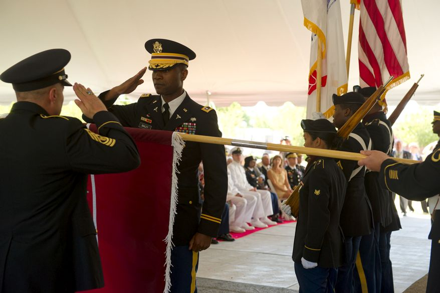 U.S. Army officers salute as they uncase one of the two new Walter Reed Army Medical Center flags that during a ceremony Wednesday, July 27, 2011 to officially mark the transition to medical services at Bethesda Naval Medical Center and Ft. Belvoir. The official close date of Walter Reed is Sept. 15. (Barbara L. Salisbury/The Washington Times)