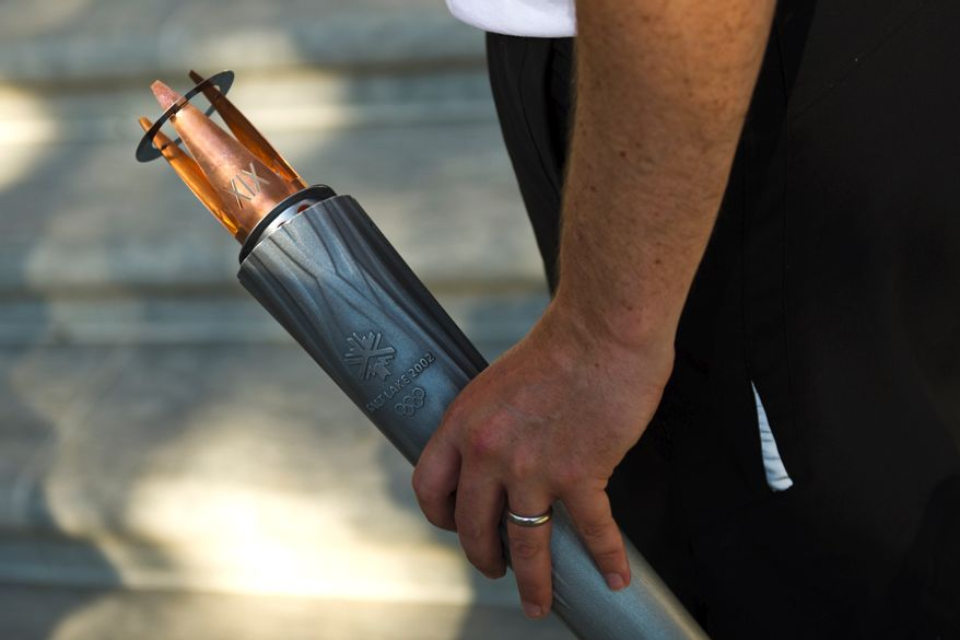 "Chris Keay, an employee of the British Embassy, holds an Olympic Torch, from the 2002 Games in Salt Lake City, prior to the run from the Canadian Embassy to the British Embassy, in Washington, D.C., Wednesday, July 27, 2011. Wednesday marked the ""One Year to Go"" mark to the 2012 Summer Olympic Games in London.  (Drew Angerer/The Washington Times)"