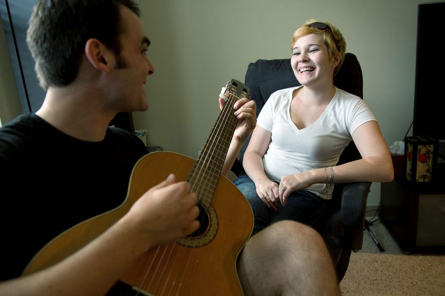 ROD LAMKEY JR./THE WASHINGTON TIMES Jesse McLaughlin serenades his roommate and girlfriend, Lisa Harbin, in their Arlington apartment. He's a finalist in Apartments.com's ongoing national Roommate of the Year contest. He helps keep the apartment clean and is considerate and always on time with the rent, the opposite of the roommate from hell pop culture sometimes depicts.