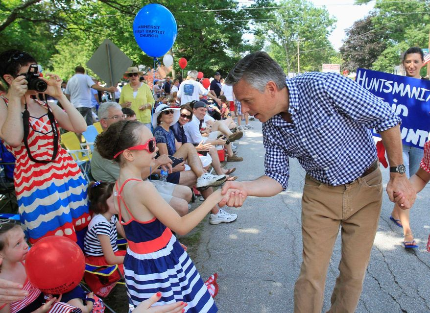 Former Utah Gov. Jon Huntsman Jr., who is running for the Republican presidential nomination, shakes hands with Molly Graybill while marching in a July Fourth parade in Amherst, N.H. (AP Photo)