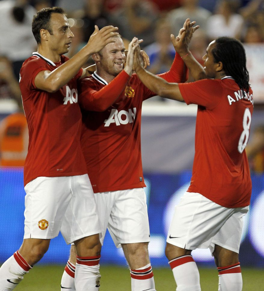 Manchester United's Anderson is congratulated by teammates Dimitar Berbatov  and Wayne Rooney after scoring a goal against the MLS All-Stars. Man U won 4-0 and will play Barcelona in a friendly Saturday night. (AP Photo/Julio Cortez)