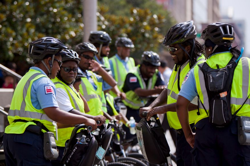 Parking enforcement officers ride their bikes and segways just before Mayor Vincent C. Gray announced the completion of pay-by-phone parking across the District, in Chinatown on Thursday, July 28, 2011. (Pratik Shah/The Washington Times)