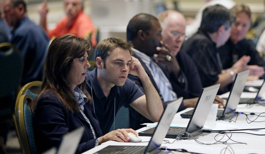 ** FILE ** In this July 26, 2011, photo, workers seeking employment create resumes and look for open positions on laptops provided by USAJobs at a job fair for space workers and those workers that lost jobs due to the end of the space shuttle program in Cape Canaveral, Fla. (AP Photo/John Raoux)