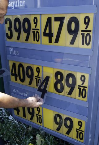 **FILE** In this photo from June 21, 2011, Shell gas worker Toke Fusi changes gas prices down at a Shell gas station in Menlo Park, Calif. (Associated Press)