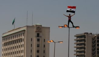 A protester waves an Egyptian flag from the top of a street lamp on July 29, 2011, during a demonstration in Cairo after Friday prayers in Tahrir Square. Many Egyptians have rallied in the main city square seeking to unify their demands despite rifts over key issues between liberal activists and Islamist groups. (Associated Press)