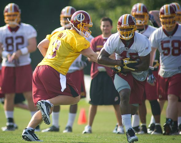 Washington Redskins quarterback John Beck (3) rolls out and hands the ball off to running back Ryan Torain (46) during the first day of training camp at Redskins Park in Ashburn, Va., Friday, July 29, 2011. (Rod Lamkey Jr./The Washington Times)