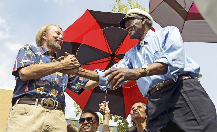 ASSOCIATED PRESS PHOTOGRAPHS Civic leader Joe Edwards (above left) shakes hands with Chuck Berry after introducing Mr. Berry during the dedication of a statue of the musician on Friday. The music legend receives congratulations from fans after the dedication (left).