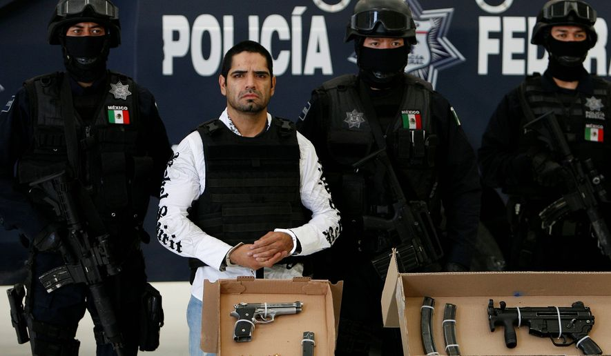 """** FILE ** Jose Antonio Acosta Hernandez gets the customary Mexican """"perp walk"""" by federal police officers in Mexico City after his arrest. Mr. Acosta, a former federal police officer, was one of Mexico's most-wanted. (Associated Press)"""