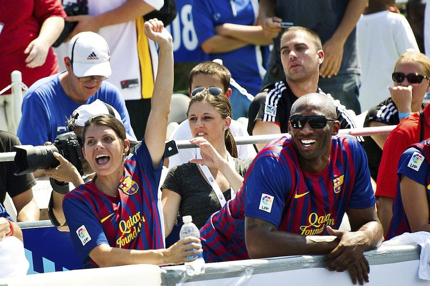 """Former U.S. Soccer player Mia Hamm and Los Angeles Lakers star Kobe Bryant watch from the sidelines during a charity soccer match Sunday in the District. """"Washington comes out and gets involved,"""" Ms. Hamm said."""