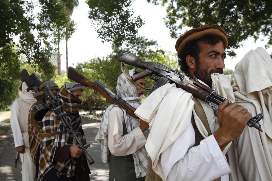 ** FILE ** Taliban fighters hold their weapons on July 31, 2011, in Jalalabad, east of Kabul Afghanistan. (Associated Press)