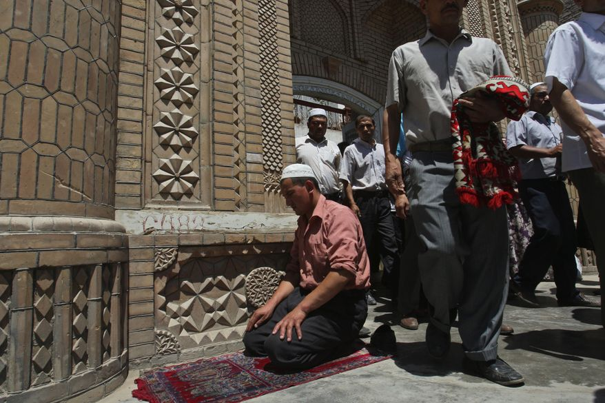 **FILE** In this photo from July 10, 2009, Muslim worshipers come out of a mosque after noon prayers in Kashgar, China. (Associated Press)