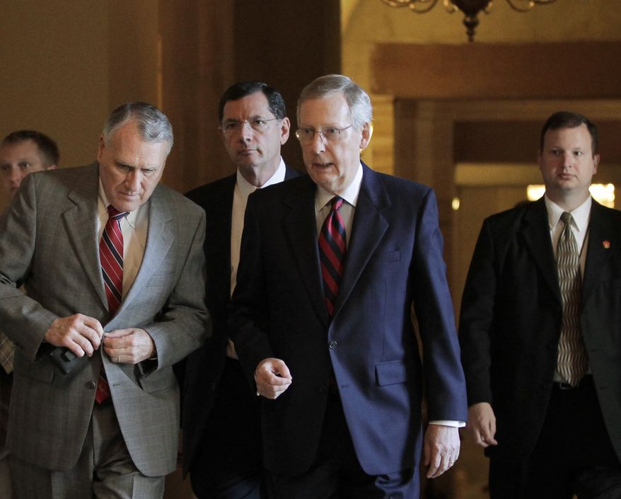 Senate Minority Leader Mitch McConnell (second from right), Kentucky Republican, walks July 31, 2011, to the Senate floor at the Capitol for a vote on a debt-limit solution crafted by Senate Majority Leader Harry Reid. McConnell is joined by Senate Republican Whip Jon Kyl (left), of Arizona, and Sen. John Barrasso (rear center), Wyoming Republican. (Associated Press)