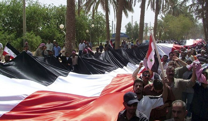 In this photo released by the Syrian official news agency SANA, Syrian pro-government supporters carry a giant national flag during a rally in the eastern province of Deir el-Zour, Syria, on July 28, 2011. (Associated Press/SANA)