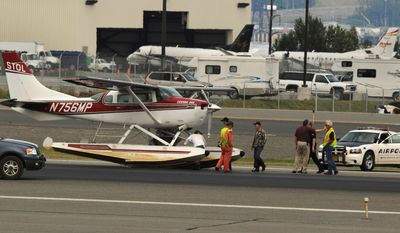 A float plane sits on the side of the runway at Ted Stevens International Airport in Anchorage Alaska after making an emergency landing on July 30, 2011. The plane collided mid-air with a Cessna 180 in the Trapper Creek area. The Cessna 180 crashed to the ground and burned, killing at least two people on board, authorities said. (Associated Press)